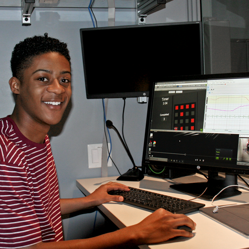 Photo of Black male undergraduate student sitting at a computer in a laboratory.